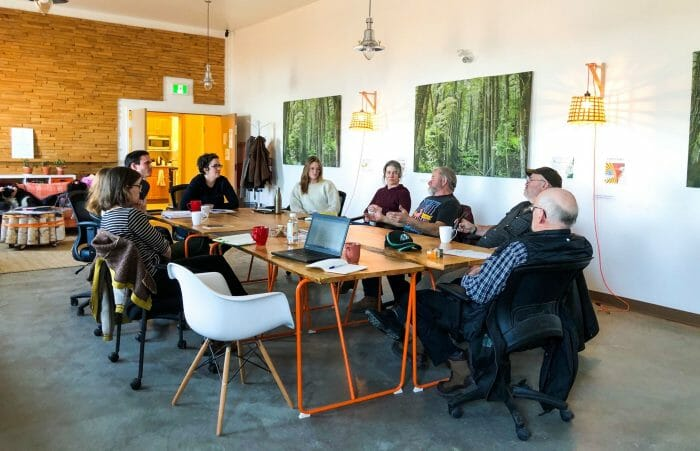 A group of woodlot owners meet around a table.