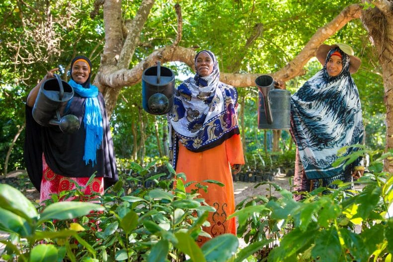 Three women holding up watering cans looking at the camera