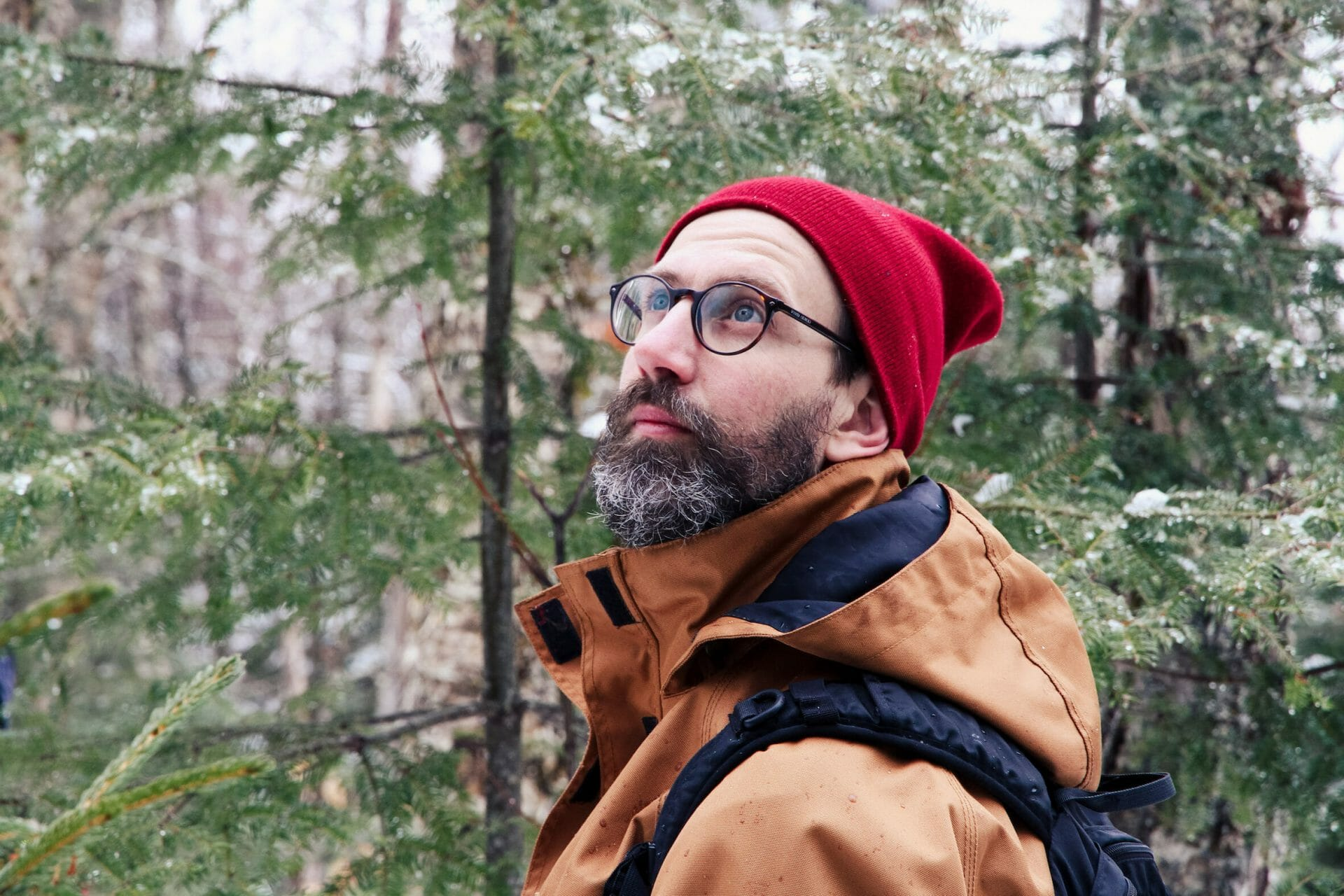 A man with round glasses and a red hat looks up at the forest canopy.
