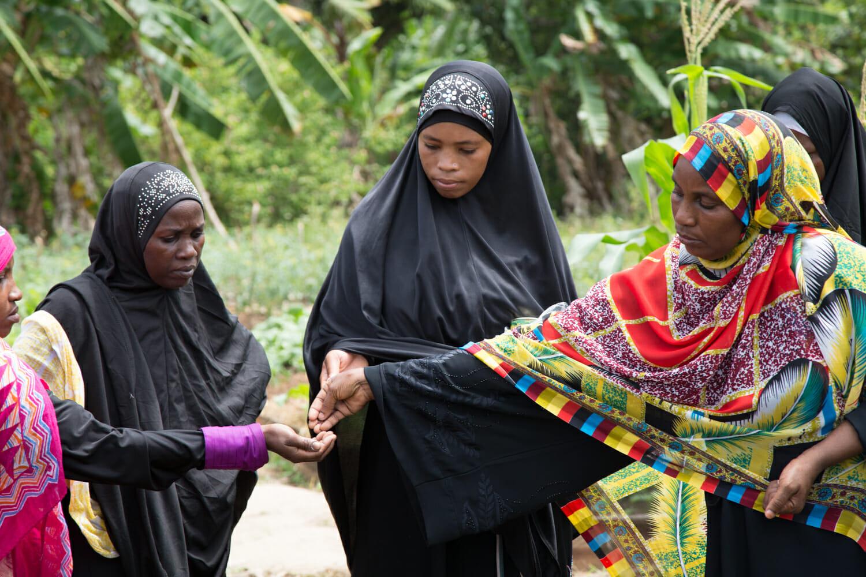 Zanzibari women sharing seeds